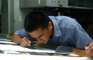 Print Operator Checking Details On Printed Materials.